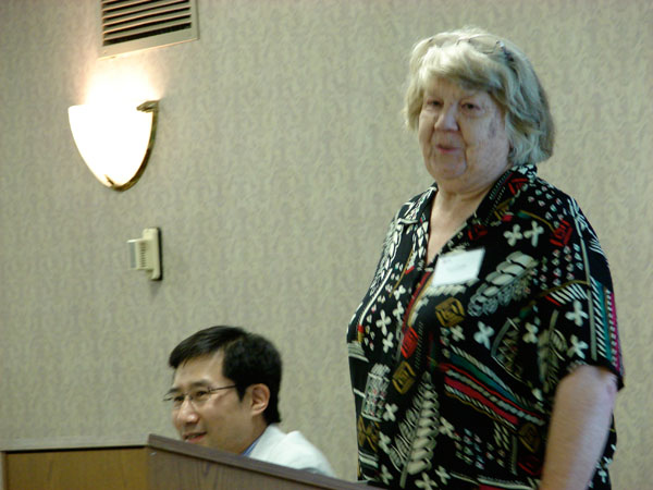 older woman talking to group of people at a podium