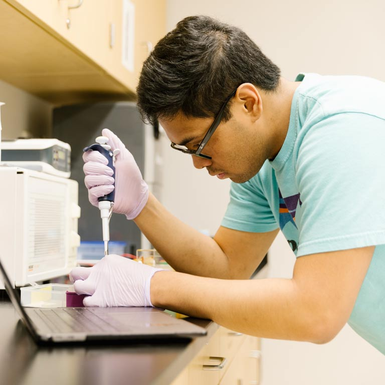 male student in blue shirt pouring liquid from a pipette into a test tube