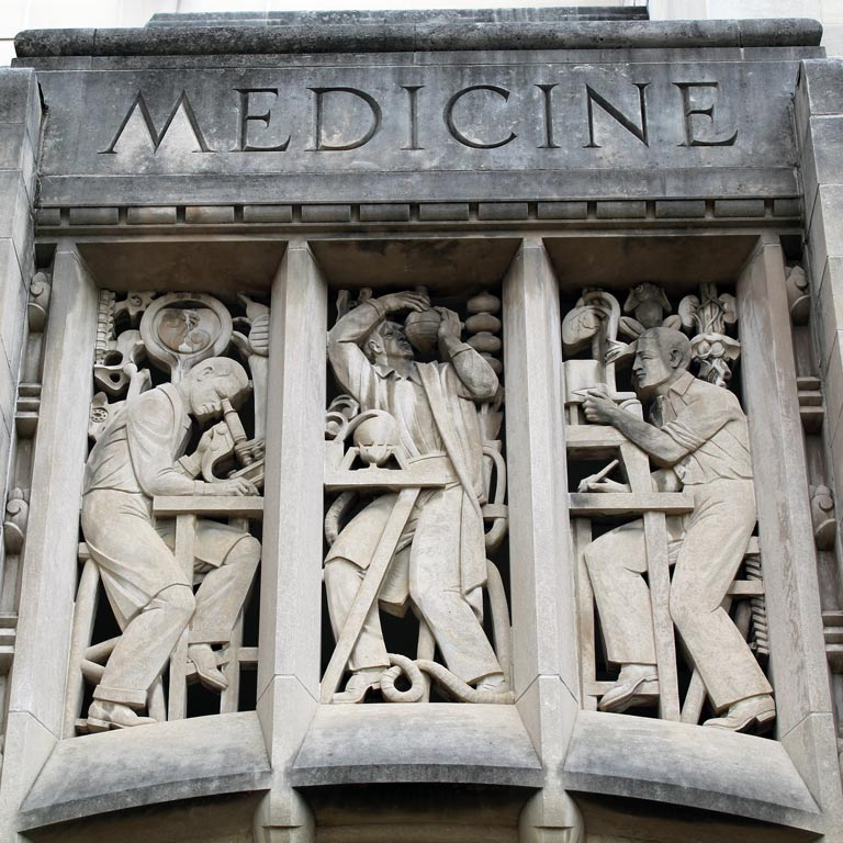 Scientific sculptures carved in the side of building with carved word Medicine